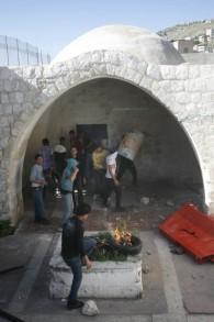 De jeunes Palestiniens masqués brûlent des pneus et jettent des pierres au Tombeau de Joseph pendant des affrontements contre les troupes israéliennes, à Naplouse, en avril 2011. (Crédit : Issam Rimawi/Flash90)