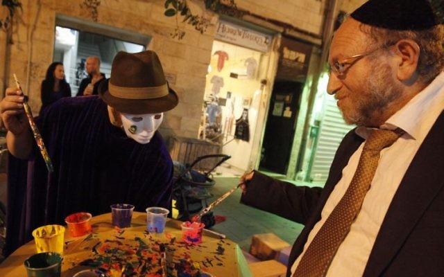 """Un ultra-orthodoxe et un artiste pendant le festival annuel """"Manofim"""", à Jérusalem. Illustration. (Crédit : Miriam Alster/Flash90)"""