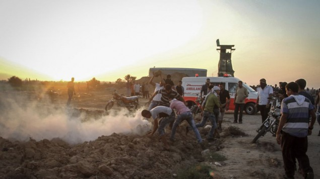 Des manifestants palestiniens affrontent les soldats israéliens près de la clôture de sécurité entre Israël et le sud de la bande de Gaza, à l'est de Khan Yunis, le 16 octobre 2015. (Crédit : Abed Rahim Khatib/Flash90)