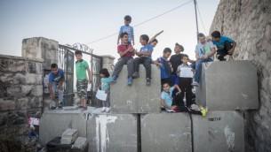 Des enfants palestiniens posent pour une photo au-dessus des blocs de ciment placés par l'armée israélienne dans le quartier de Ras al Amud de Jérusalem-Est, le 21 octobre 2015. (Crédit : Hadas Parush / Flash90)