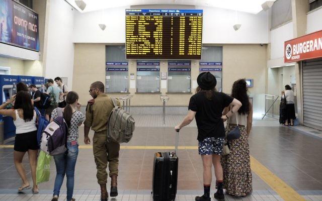 Les voyageurs à la gare centrale de Savidor à Tel Aviv regardant les horaires, où aucun train vers le nord sont indiqués, le 3 septembre 2016 (Crédit : Tomer Neuberg / Flash90)