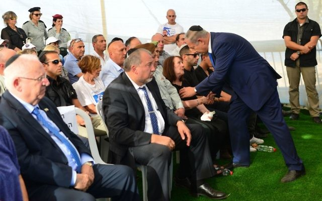 Le Premier ministre Benjamin Netanyahu s'adresse à Zehava Shaul pendant les funérailles de son mari, Herzl Shaul, au cimetière de Poria Illit, dans le nord d'Israël, le 4 septembre 2016. (Crédit : Kobi Gideon/GPO)