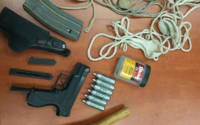 Un pistolet à air comprimé, un chargeur et d'autres objets saisis par la police au domicile d'un suspect israélien accusé d'avoir tiré avec le pistolet sur un véhicule palestinien en août 2016. (Crédit : police israélienne)