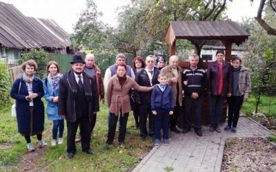 Les habitants de Vishnyeva, en Biélorussie, se rassemblent devant la maison d'enfance de Shimon Peres pour lui rendre un dernier hommage après son décès, le 28 septembre 2016. (Crédit : Limmud FSU)