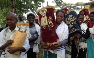 Anticipant la construction d'une nouvelle synagogue à Nabagoye, en Ouganda, les femmes et les enfants ont l'honneur de transférer les rouleaux de la Torah, de la vieille synagogue à une maison temporaire. (Autorisation de Be'chol Lashon, via JTA)