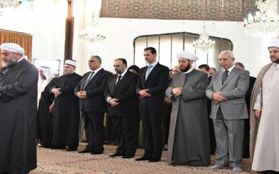 Le président syrien Bashar el-Assad (4° à droite) pendant les prières de l'Aïd al-Fitr à Homs, le 6 juillet 2016. (Crédit : SANA)