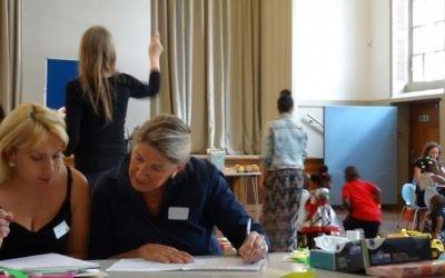 Des bénévoles aident les réfugiés à remplir des formulaires, pendant que les enfants jouent, au centre d'accueil de la West London Synagogue