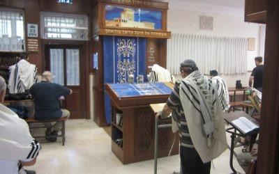 Un homme prie dans une synagogue. Illustration. (Crédit : Ben Sales/JTA)