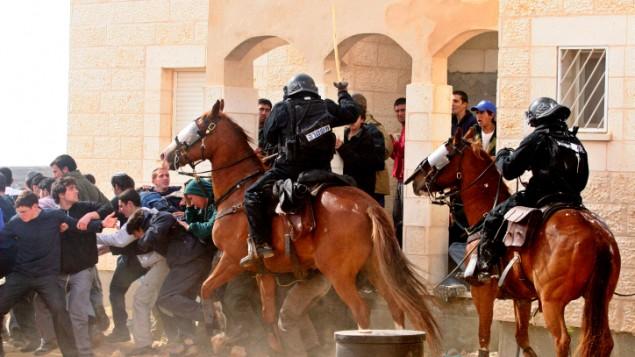 Des policiers israéliens affrontent des habitants juifs sur une barricade en feu dans l'avant-poste non autorisé d'Amona, proche de l'implantation juive d'Ofra, en Cisjordanie, le 1er janvier 2006. (Crédit : Pierre Terdjman/Flash90)