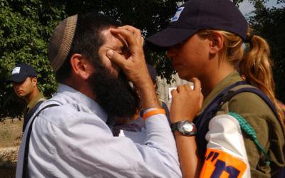 Un résident juif d'une implantation argumente avec une soldate pendant le désengagement de la bande de Gaza, le 17 août 2005. (Crédit : Yossi Zamir/Flash90)
