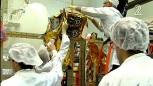 Les employés d'Israel Aerospace Industries construisant le satellite Amos-6 dans des images diffusées le 1er septembre  2016. (Crédit : capture d'écran Deuxième chaîne)
