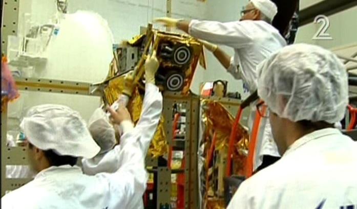 Les employés d'Israel Aerospace Industries construisant le satellite Amos-6 dans des images diffusées, le 1er septembre  2016 (Crédit : Capture d'écran Deuxième chaîne)