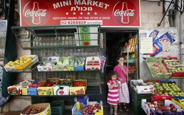 Deux jeunes filles mangent de la crème glacée devant une épicerie à Jérusalem, le 2 août 2010 (Crédit : Miriam Alster / Flash90)
