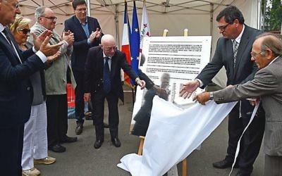 Jacques Stuzalft, à gauche, aide à dévoiler une plaque rappelant le sauvetage des enfants juifs de Lille, en France, par les travailleurs des chemins de fer locaux lors d'une cérémonie dans la ville française du nord, le 9 septembre 2016. (Crédit : Ville de Lille, via Facebook)
