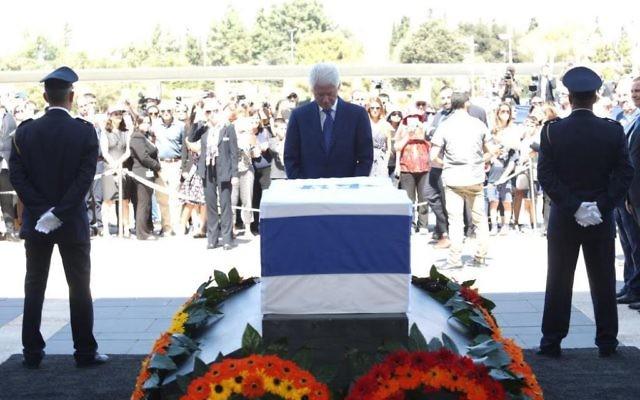 Bill Clinton se recueille sur le cercueil de Shimon Peres, le 29 septembre 2016 sur le parvis de la Knesset (Crédit :  bureau de Yizhak Harari / Knesset porte-parole)
