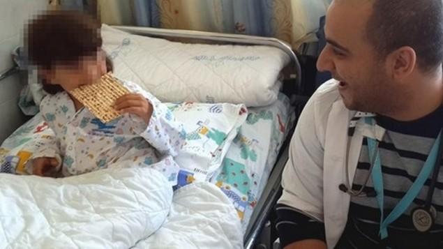 Un garçon syrien hospitalisé en Israël goûte sa première matza, le 7 avril 2015. (Crédit : hôpital Ziv)