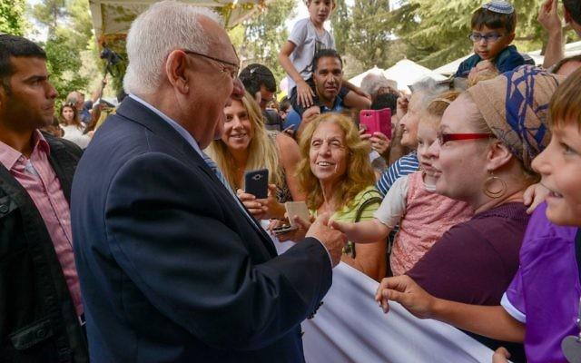 """Le président israélien Reuben Rivlin accueille les visiteurs lors de la """"Soucca ouverte"""" à Jérusalem, le 19 octobre 2016. (Crédits : Roy Berkovich / GPO)"""