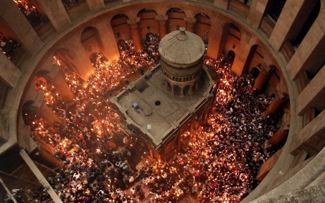 Des fidèles chrétiens orthodoxes allument des bougies dans l'église du Saint-Sépulcre de la Vieille Ville de Jérusalem, pendant la Pâque orthodoxe, le 30 avril 2016. (Crédit : Thomas Coex/AFP)