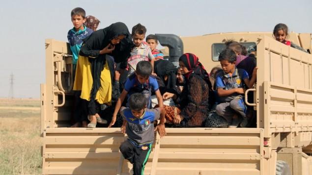 Des familles irakiennes déplacées descendent d'un camion à leur arrivée dans une zone contrôlée par les forces Peshmerga, à 55 km à l'ouest de la ville irakienne de Kirkouk, après avoir quitté leur village de Hawija pour échapper aux jihadistes du groupe Etat islamique, le 21 août 2016. (Crédit : AFP/Marwan Ibrahim)