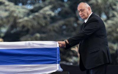 Chemi Peres devant le cercueil de son père, l'ancien président Shimon Peres, au cimetière national du mont Herzl, à Jérusalem, le 30 septembre 2016. (Crédit : AFP/Nicholas Kamm)