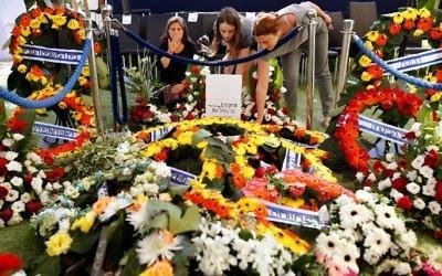 Des Israéliennes sur la tombe de l'ancien président Shimon Peres, après son enterrement au cimetière national du mont Herzl, à Jérusalem, le 30 septembre 2016. (Crédit : AFP/Gil Cohen-Magen)