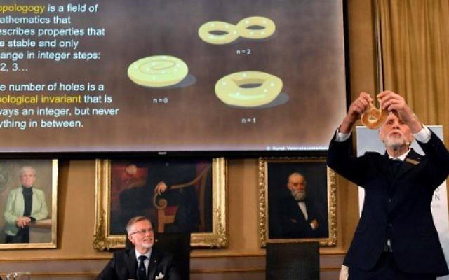 Thors Hans Hansson (à droite), membre du Comité Nobel pour la physique, utilise un bretzel pour illustrer ses explications lors d'une conférence de presse pour annoncer les gagnants du Prix Nobel de physique 2016 à l'Académie royale suédoise des sciences à Stockholm, en Suède, le 4 octobre 2016 (Crédit : AFP PHOTO / TT AGENCE DE NOUVELLES / Anders WIKLUND / Suède OUT)