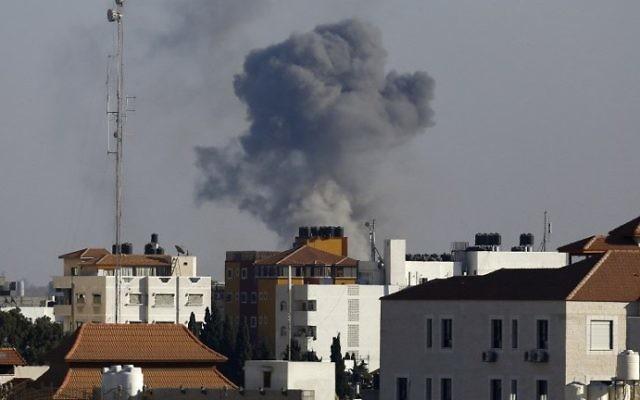 La fumée monte depuis l'est de Gaza Ville après une frappe militaire israélienne sur une position du Hamas, en représailles après un tir de roquette, le 5 octobre 2016. (Crédit : AFP/Mahmud Hams)