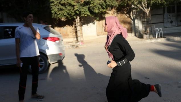 Une jeune palestinienne sort en courant de chez elle dans le quartier de Shejaiya, à l'est de Gaza Ville, après une frappe de représailles israélienne, le 5 octobre 2016. (Crédit : AFP/Mohammed Abed)