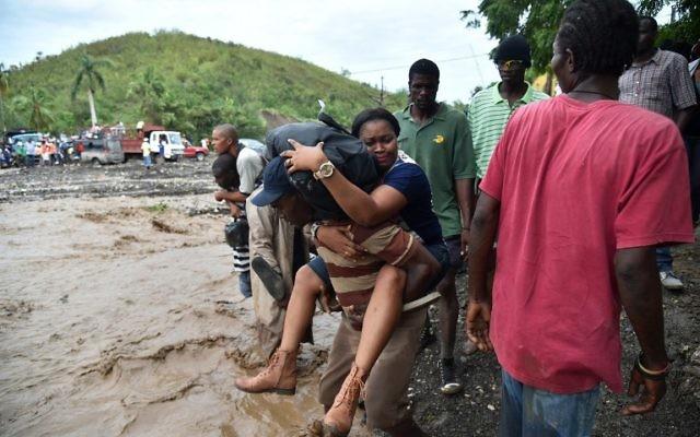 Des habitants de Haïti traversent la rivière La Digue, à Petit Goave, où le pont s'est effondré à cause de la pluie apportée par l'ouragan Matthew, au sud ouest de Port-au-Prince, le 6 octobre 2016. (Crédit : AFP/Hector Retamal)