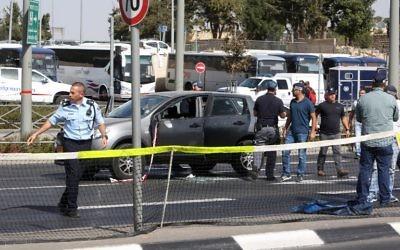 La police scientifique israélienne collecte des preuves dans la voiture appartenant à une victime après une attaque à main armée près du siège de la police à Jérusalem, le 9 octobre 2016. (Crédit : AFP/Menahem Kahana)