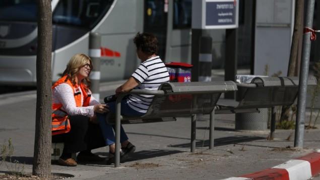 Une secouriste israélienne aide une femme sur la scène d'une attaque terroriste à main armée à Jérusalem, le 9 octobre 2016. (Crédit : AFP/Ahmad Gharabli)