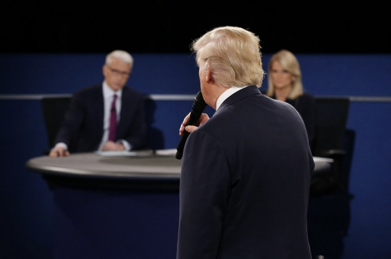 Les présentateurs Anderson Cooper de la CNN (à gauche) et Martha Raddatz d'ABC écoutant le candidat républicain à la présidentielle Donald Trump pendant le deuxième débat à l'université de Washington à St. Louis, Missouri, le 9 octobre 2016 (Crédit : AFP PHOTO / POOL / JIM BOURG)