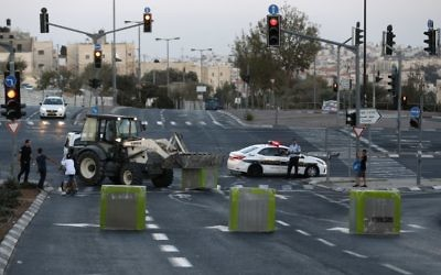 Des blocs de béton sont installés par les forces israéliennes sur une route reliant le quartier arabe de Jérusalem Est de Beit Hanina à Jérusalem Ouest, avant Yom Kippour, le 11 octobre 2016. (Crédit : AFP/Ahmad Gharabli)