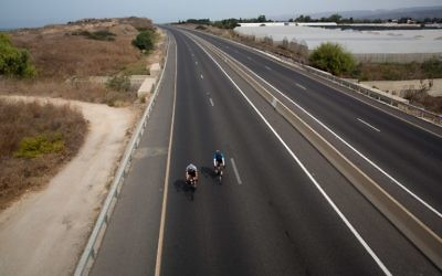 Des Israéliens en vélo sur une autoroute près du moshav Habonim dans le nord d'Israël, à Yom Kippour, le 12 octobre 2016. (Crédit : AFP/Menahem Kahana)