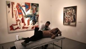 Luke Wessman tatoue un vétéran de la guerre Yogev Meushar, qui a été blessé en 2006 dans une embuscade palestinienne dans une ville de Cisjordanie, au Musée d'Israël à Jérusalem, le 20 octobre 2016. (Crédit : AFP / Menahem Kahana)