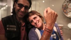 Kay Wilson montre une prière tatouée en hébreu sur son poignet, faite par le célèbre tatoueur Wassim Razzouk, un chrétien palestinien de la Vieille Ville de Jérusalem, dans le cadre d'une initiative visant à utiliser l'art pour guérir les blessures mentales et physiques dans une salle d'exposition d'art moderne dans le musée d'Israël à Jérusalem, le 20 octobre 2016. (Crédit : AFP / MENAHEM KAHANA)
