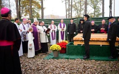 L'archevêque de Maribor, Alojzij Cvikl (4° à gauche), bénit un cercueil pendant une cérémonie marquant le début des funérailles de quelques 800 personnes assassinées par les forces communistes après la Seconde Guerre mondiale au parc mémoriel de Dobrava, à Maribor, en Slovénie, le 27 octobre 2016. (Crédit : AFP/Jure Makovec)
