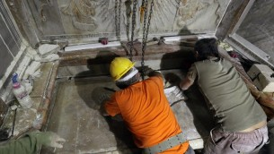 Des experts en restauration replace la plaque de marbre qui couvrait le Tombeau de Jésus, où son corps aurait été enterré, après son ouverture pendant trois jours pour permettre sa restauration et son étude, à Jérusalem, le 28 octobre 2016. (Crédit : AFP/Gali Tibbon)