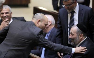 Moshe Kahlon, président de Koulanou (à gauche), Naftali Bennet, chef de HaBayit HaYehudi (au centre) et Aryeh Deri, dirigeant de Shas ( à droite) pendant une session parlementaire où le Premier ministre Benjamin Netanyahu a proposé son gouvernement à un vote de confiance, à la Knesset, le 14 mai 2015. (Crédit : AFP/Pool/Jim Hollander)
