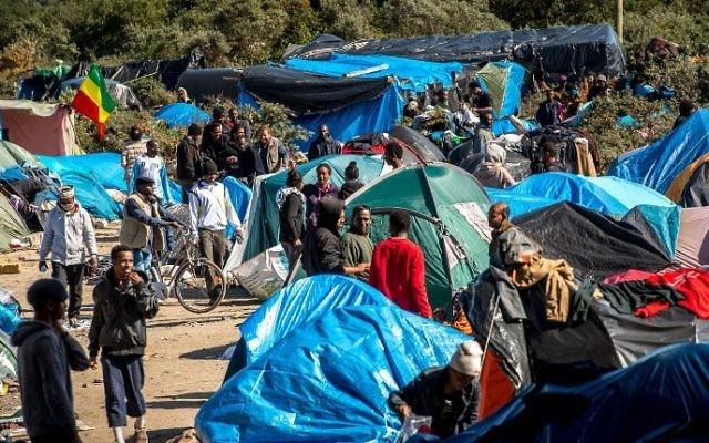 """Des migrants sur le site surnommé la """"Nouvelle Jungle"""" où 3 000 personnes se sont installées ; la plupart d'entre eux cherchent désespérément à entrer au Royaume-Uni, à Calais, en France, le 19 septembre 2015. (Crédit : Philippe Huguen/AFP)"""