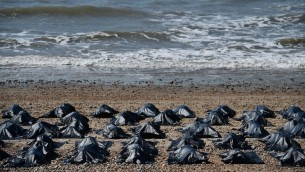Des sacs mortuaires parsèment la plage de Brighton, au sud de l'Angleterre, le 22 avril 2015. Cette mise en scène, par Amnesty International était destinée a mettre en lumière la réponse de la Grande-Bretagne à la crise des réfugiés et des migrants dans la méditerannée, qui a été qualifiée d'honteuse. (Crédit photo : Ben Stansall/AFP)