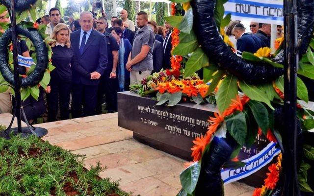 Benjamin Netanyahu et son épouse Sara devant la pierre tombale de Shimon Peres au cimetière du mont Herzl à Jérusalem, le 28 octobre 2016 (Crédit : חיים צח, לע״מ)