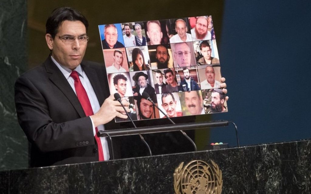 L'ambassadeur d'Israël à l'ONU, Danny Danon, tient un collage de photos des victimes du terrorisme israéliens tués pendant la montée continue de la violence depuis la mi-septembre, le 23 novembre 2015 (Crédit :  ONU / Cia Pak)