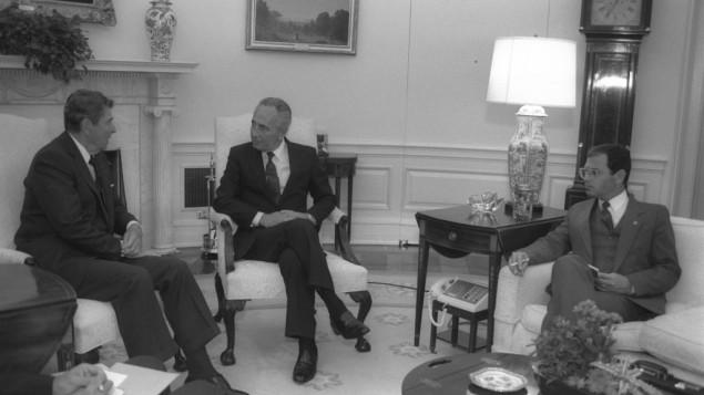 Ronald Reagan, président des Etats-Unis, et le Premier ministre Shimon Peres. Le conseiller politique de Peres, Nimrod Novik, prend des notes, à la Maison Blanche, le 15 septembre 1986. (Crédit : Saar Yaacov/GPO)