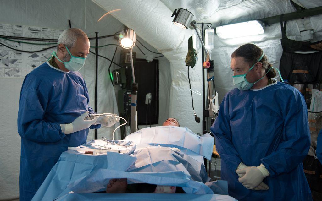 """Deux médecins militaires israéliens réalisent une """"chirurgie"""" pendant un exercice d'hôpital de campagne dans le nord d'Israël, en septembre 2016. (Crédit : unité des porte-paroles de l'armée israélienne)"""