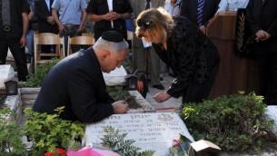 Le Premier ministre Benjamin Netanyahu et son épouse Sara sur la tombe de son frère Yoni Netanyahu, tué pendant l'opération Entebbe en 1976, le 28 juin 2006. (Crédit : Moshe Milner/GPO/Flash90)