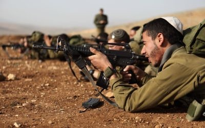 """Les soldats israéliens de l'unité """"Nahal Haredi"""" de Tsahal lors d'un exercice de tir à la base militaire de Peles dans la vallée nord du Jourdain, en août 2013.(Crédit : Yaakov Naumi/Flash90)"""