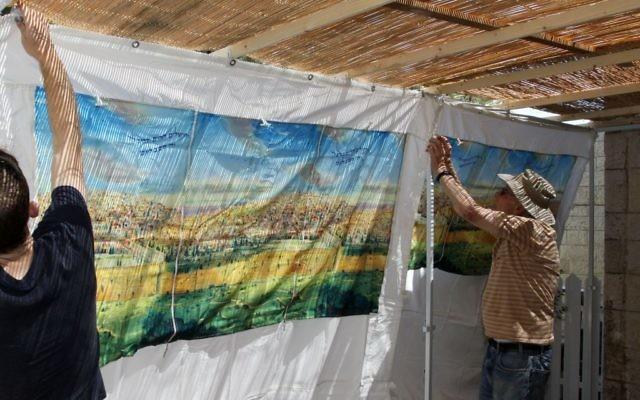 Photo d'illustration. Un grand-père et son petit-fils construisent une soucca dans l'implantation d'Efrat, en septembre 2013. (Crédits : Gershon Elinson / Flash90)