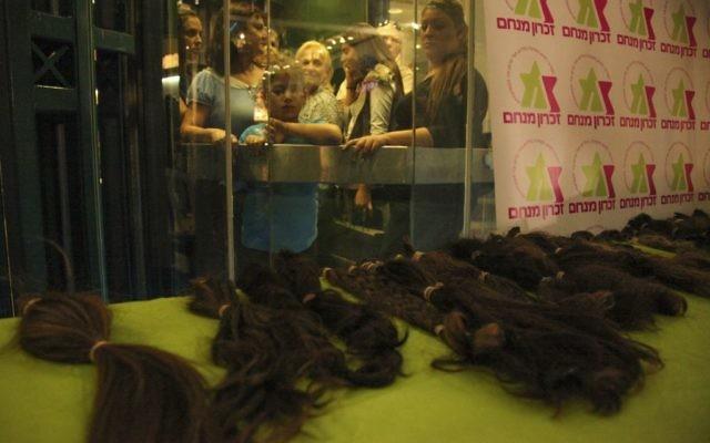 Dons de cheveux pour des perruques destinés à des enfants souffrant d'un cancer pendant un évènement organisé par Zichron Menachem, l'association israélienne de soutien aux enfants avec un cancer et à leurs familles. Illustration. (Crédit : Meital Cohen/Flash90)