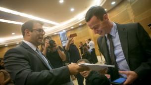 Oren Hazan, député du Likud (à gauche), remet à Amit Segal, journaliste de la Deuxième chaîne, une copie de la plainte pour diffamation que le député a porté contre le journaliste, le 12 octobre 2015. (Crédit : Miriam Alster/Flash90)